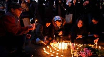 TRAGIK: Penduduk tempatan menyalakan lilin bagi memperingati mangsa Boeing 737 Ukraine International Airlines pada perhimpunan di hadapan Universiti Amirkabir di Tehran, Iran kelmarin. — Gambar AFP
