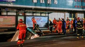 MENGERIKAN: Gambar yang dirakam kelmarin menunjukkan anggota penyelamat cuba mengangkat keluar bas yang tenggelam di dalam lubang benam di sebatang jalan di Xining, wilayah barat laut Qinghai. — Gambar AFP