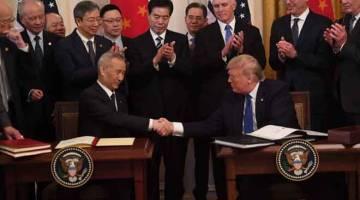 SEPAKAT: Trump (kanan) dan Liu He berjabat tangan semasa majlis menandatangani perjanjian perdagangan di Rumah Putih di Washington, DC, Amerika Syarikat kelmarin. — Gambar AFP
