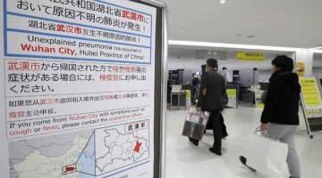 AMARAN: Penumpang berjalan melintasi papan tanda, yang memberi amaran mengenai penularan virus misteri di bandar Wuhan, China, di Lapangan Terbang Narita di Chiba, Jepun kelmarin. — Gambar AFP