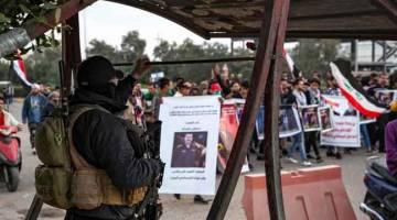 PROTES: Anggota polis mengawasi penunjuk perasaan yang berarak semasa protes antikerajaan, turut menggesa untuk kebebasan media, di bandar Basra di selatan Iraq kelmarin. — Gambar AFP