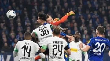 PENUH AKSI: Sebahagian daripada babak-babak aksi perlawanan Bundesliga Jerman di antara Schalke dan Moenchengladbach di Gelsenkirchen. — Gambar AFP