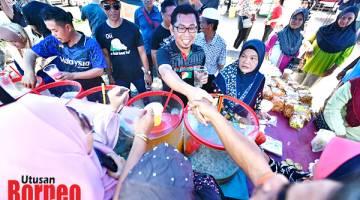 MESRA: Mohamad (tengah) menyantuni rakyat yang mengunjungi Tamu Pekan Membakut.