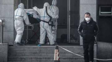 SERIUS: Kakitangan perubatan mengusung masuk seorang pesakit ke dalam Hospital Jinyintan yang menempatkan unit rawatan virus misteri mirip SARS itu di Wuhan, wilayah tengah Hubei pada Sabtu lalu. — Gambar AFP