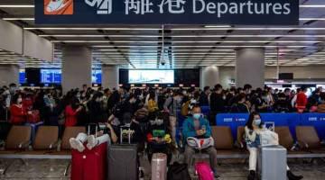 BERHATI-HATI: Orang ramai memakai topeng perlindungan berbaris di balai berlepas stesen kereta api Kowloon Barat di Hong Kong, semalam. — Gambar AFP