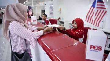 MELAYAN PELANGGAN: Petugas Pos Malaysia Nurul Fazliana Termazi (kanan) melayan pelanggan Nurul Usaimah Shamsul Kamar (kiri) yang membuat urusan pos ketika tinjauan fotoBernama di Ibu Pejabat Pos Malaysia, Kuala Lumpur, semalam. — Gambar Bernama