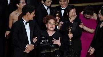 LAKAR SEJARAH: Penerbit Parasite Kwak Sin-ae (tiga kanan) bersama para pelakon dan kru menerima anugerah filem terbaik pada Oscar Ke-92 di Dolby Theater in Hollywood, California kelmarin. — Gambar AFP