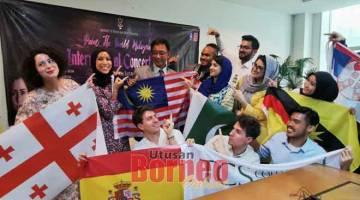 NEMUAI MERI BASA: Abdul Karim begambar enggau tim Paint the World Malaysia ti betuaika Aziza (bediri, kiba)sereta disempulang ke bukai pengudah nemuai meri basa, ensanus.-— Gambar Roystein Emmor