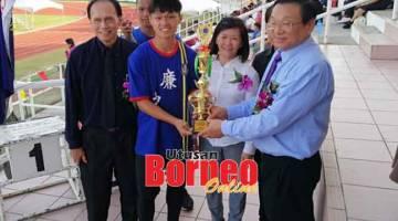 TAHNIAH: Dr Teo (kanan) menyampaikan piala kepada wakil atlet RRSS dan disaksikan Ketua Pegawai Eksekutif RRSS, Pauline Ho (kanan kedua) dan Pengetua RRSS, Richard Liu (kiri). RRSS muncul juara keseluruhan MSSS Miri di Stadium Miri semalam.