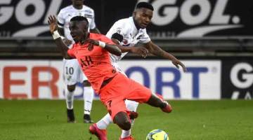 TERJAHAN KERAS: Penyerang Amien, Sehrou Guirassy (kanan) menjatuhkan pemain PSG, Idrissa Gueye ketika bersaing pada perlawanan liga di Stadium Licorne, Amiens kelmarin. — Gambar AFP