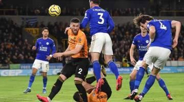 PERCUBAAN TEPAT: Pemain pertahanan Leicester City, Caglar Soyuncu (kanan) melakukan tandukan ke arah pintu gol  Wolverhampton Wanderers ketika beraksi pada perlawanan Liga Perdana Inggeris di Stadium Molineux, Wolverhampton kelmarin. Keputusan penuh 0-0. — Gambar AFP