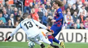 GOL!:   Griezmann  (kanan) berjaya melepasi halangan daripada penjaga gol Getafe, David Soria untuk menjaringkan gol pada perlawanan La Liga di Nou Camp, Barcelona kelmarin. — Gambar AFP