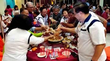 BESERAKUP MIH KITAI: Dr Annuar (tengah), Lau (lima kiba) enggau raban ke bukai lebuh ti ngirau 'Yee Sang' ba Pengerami Makai Lemai Taun Baru China Serakup KMKK China Pampang Sibu, apin lama ti udah.