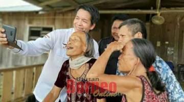 SELFIE: Dennis enggau peranak Penan di Long Sempat beselfie pengudah bejadi projek SARES di Long Sengong, Ulu Tinjar.