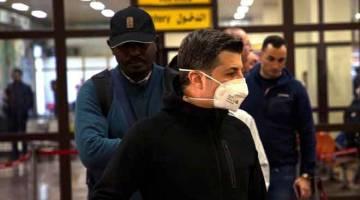 SEKATAN: Penumpang memakai topeng muka dilihat di lapangan terbang Basra di selatan Iraq baru-baru ini. Pihak berkuasa Iraq kelmarin melarang perjalanan keluar dan masuk dari Iran selepas dua lelaki disahkan mati akibat COVID-19. — Gambar AFP