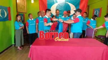 KELUAR PARTI: Hasrol (kiri) bersama beberapa ahli PKR Tanjung Manis melipat bendera PKR sebagai simbolik keluar parti semalam.