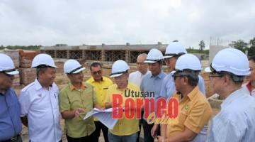Dr Sim (lima dari kiri) diberi penerangan oleh wakil dari HDC mengenai pelaksaan dua projek jalan masuk di Sibu Jaya sambil diperhatikan oleh yang lain.