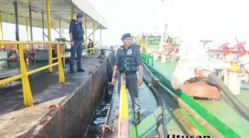 ANGGOTA: Polis Marin memeriksa muatan kapal.