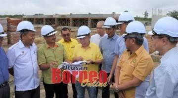 Dr Sim (lima dari kiri) diberi penerangan oleh wakil dari HDC mengenai pelaksanaan dua projek jalan masuk di Sibu Jaya .