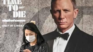 DITANGGUHKAN: Gambar fail bertarikh 27 Februari 2020 ini menunjukkan seorang wanita memakai topeng muka di tengah-tengah kebimbangan novel koronavirus  COVID-19 berdiri di hadapan poster filem baharu James Bond, 'No Time to Die' di Bangkok. Tayangan filem baharu James Bond ditangguhkan, studio-studio membatalkan festival filem manakala produksi filem blokbuster ditutup berikutan kebimbangan penularan virus COVID-19. — Gambar AFP