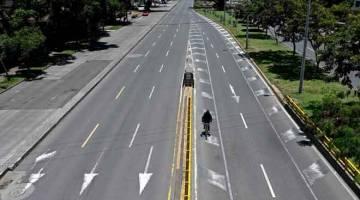 LENGANG: Seorang lelaki menunggang basikal di lebuh raya Cali yang kosong berikutan sekatan di Colombia, kelmarin bagi membendung COVID-19. — Gambar AFP