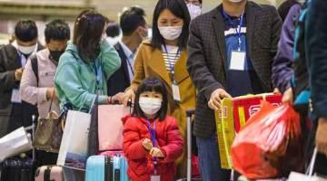 TIADA LAGI SEKATAN: Pekerja asing bersama keluarga mereka berbaris untuk menaiki kereta api khas ke Shenzhen, di Yichang, wilayah tengah Hubei kelmarin. China mengumumkan sekatan perjalanan ditarik balik di wilayah tersebut selepas perintah berkurung selama dua bulan untuk membendung COVID-19. — Gambar AFP