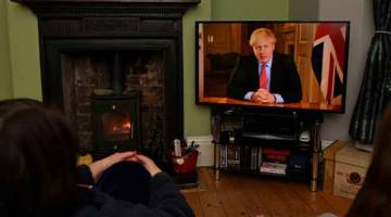 PESANAN PENTING: Penghuni di sebuah rumah di Liverpool, barat laut England, menonton                    televisyen ketika Johnson menyampaikan ucapan dari 10 Downing Street di London kelmarin untuk menggesa orang ramai duduk di rumah dalam usaha membendung penularan wabak COVID-19. — Gambar AFP
