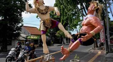 SUASANA SEPI: Penduduk menunggang motosikal melintasi patung dikenali sebagai Ogoh-Ogoh menjelang sambutan 'Hari Sepi' di Denpasar, Bali kelmarin. — Gambar AFP