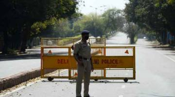 KAWALAN KETAT: Seorang anggota polis bersenjata dilihat berkawal di jalan raya sehari selepas kerajaan mengumumkan arahan berkurung selama 21 hari sebagai langkah pencegahan wabak COVID-19 di New Delhi, India semalam. — Gambar AFP