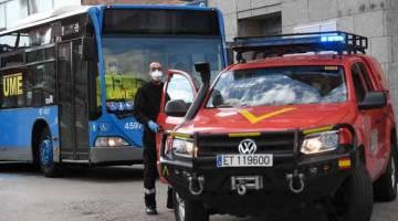 KRITIKAL: Anggota UME (Unit Kecemasan Tentera) bersiap sedia untuk memindahkan pesakit dari Klinik Hospital San Carlos dengan menaiki bas ke hospital sementara untuk pesakit COVID-19 di pusat pameran dan konvensyen Ifema di Madrid, kelmarin. — Gambar AFP