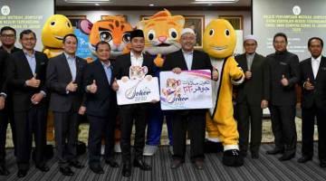 DINILAI SEMULA: Pengerusi Jawatankuasa Pelancongan, Belia dan Sukan Johor, Datuk Onn Hafiz Ghazi (lima kiri) bersama Pengerusi Jawatankuasa Pembangunan Belia, Sukan dan Badan Bukan Kerajaan Terengganu, Wan Sukairi Wan Abdullah (lima, kanan) bergambar selepas menyampaikan watikah jemputan rasmi kepada kontinjen negeri Terengganu sempena SUKMA Johor 2020 di Wisma Darul Iman, Kuala Terengganu pada 9 Mac lepas.  —Gambar AFP
