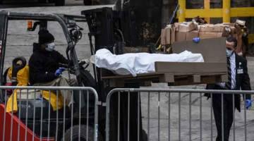 PINDAH: Pekerja menggunakan trak angkat susun untuk memindahkan mayat ke trak sejuk beku di luar Hospital Brooklyn, New York kelmarin. Akibat peningkatan dalam kes kematian COVID-19, hospital kini menggunakan trak sejuk beku sebagai rumah mayat sementara. — Gambar AFP