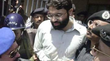 HUKUMAN DIRINGANKAN: Gambar fail diambil pada 29 Mac, 2002 menunjukkan anggota polis mengiringi Sheikh di luar mahkamah di bandar pelabuhan Karachi, Pakistan. — Gambar AFP