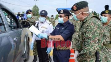 TELITI: Johnny (kanan) dan Zulkipli (dua kanan) bersama anggota                                                                                             polis dan tentera memeriksa surat kebenaran bekerja yang              dikeluarkan majikan semasa tempoh PKP bagi perkhidmatan penting di Bintulu.