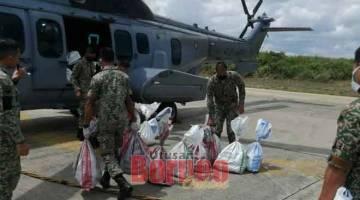 KHIDMAT: Anggota TUDM dan TDM mengangkat barang keperluan makanan ke dalam helikopter untuk diterbangkan kawasan pedalaman.