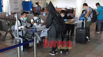 SARINGAN: Penumpang dari Labuan dan Kuala Lumpur yang tiba Lapangan Terbang Miri semalam, mengisi maklumat dan menjalani saringan sebelum dibawa ke pusat kuarantin dengan bas khas.