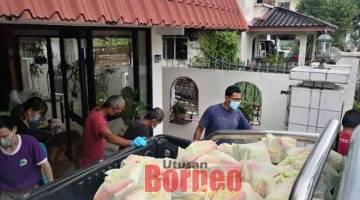 BANTUAN MAKANAN: Pasukan sukarelawan menyediakan bantuan makanan yang mahu diagihkan kepada keluarga yang memerlukan.