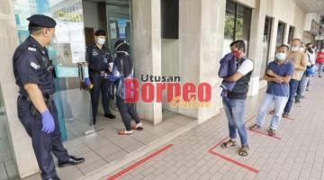 Polis Bantuan BSN memastikan para pelanggan berbaris dalam jarak 1 meter.