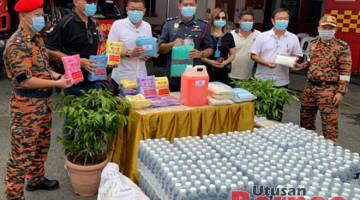 Tiong (empat kiri) bersama Wee (tiga kiri) dan Ong (dua kiri) semasa menyampaikan sumbangan di Balai Bomba dan Penyelamat Padungan, hari ini.