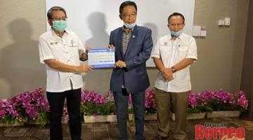 Abdul Karim menerima sumbangan Yayasan Sarawak daripada Pengarah Yayasan Sarawak, Azmi Bujang (kiri) yang disumbangkan kepada kerajaan negeri selepas sidang media di sini. Turut kelihatan Timbalan Setiausaha Kerajaan Negeri, Datu Abu Bakar Marzuki (kanan).