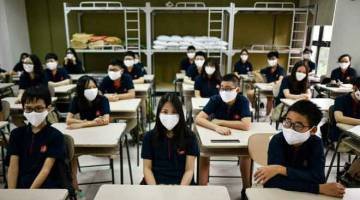 BUKA SEMULA: Para pelajar memakai topeng muka duduk menunggu guru di dalam bilik kelas di Sekolah Marie Curie di Hanoi, semalam. — Gambar AFP