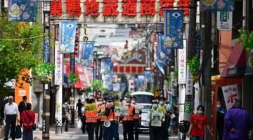 TEGAS: Pekerja perbandaran meronda sebatang jalan sambil meminta orang ramai untuk duduk di rumah semasa wabak COVID-19 di Tokyo, semalam. — Gambar AFP