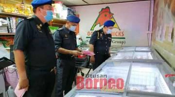 TELITI: Joe Azmi (kanan) bersama dua pegawainya sedang melakukan pemeriksaan ke atas barangan harga terkawal di salah sebuah premis di Pasar Basah Emart Tudan di sini, petang semalam.