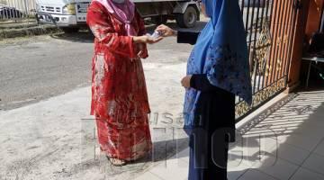 SARANAN KERAJAAN : Samsiah memberikan cecair sanitasi kepada keluarga yang datang berkunjung.