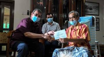 SUMBANGAN: Saifuddin (kiri) menyampaikan sumbangan kepada artis veteran Abu Bakar Juah semasa program Ziarah Kasih anjuran FINAS di kediaman artis tersebut baru-baru ini. Turut hadir adalah Ketua Pegawai Eksekutif FINAS, Ahmad Idham Ahmad Nadzri. — Gambar Bernama
