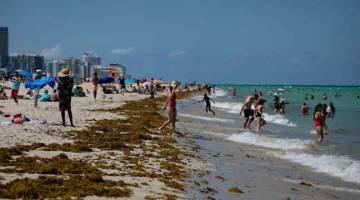 REKOD BAHARU: Gambar fail 16 Jun lalu menunjukkan orang ramai membanjiri pantai di Miami dan seminggu kemudian setakat kelmarin, negeri itu melaporkan hampir 10,000 kes jangkitan COVID-19 dalam masa 24 jam. — Gambar AFP
