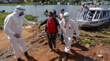 MASIH TENAT: Profesional kesihatan membantu pesakit dengan simptom COVID-19 naik ke daratan setelah bot ambulans tiba dari komuniti Vila Amazonia di Parintins, negeri Amazonas kelmarin. Parintins terkenal di seluruh dunia dengan festival dongeng rakyat Boi-Bumba yang berlangsung selama tiga hari pada lewat Jun dengan tema, kostum dan lagu berdasarkan budaya peribumi di hutan hujan Amazon. Disebabkan penularan COVID-19, festival tahun ini distrim secara langsung. — Gambar AFP