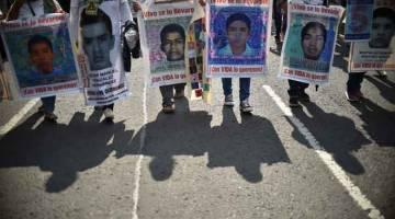 TUNTUT KEADILAN: Gambar fail menunjukkan penunjuk perasaan membawa gambar sebahagian daripada 43 pelajar yang hilang semasa berdemonstrasi di negeri Guerrero pada 26 September, 2019. — Gambar AFP