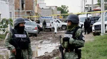 KAWALAN KETAT: Anggota Pengawal Negara dilihat berkawal selepas lelaki bersenjata membunuh 24 orang di pusat pemulihan dadah di  Irapuato, negeri Guanajuato kelmarin. — Gambar AFP