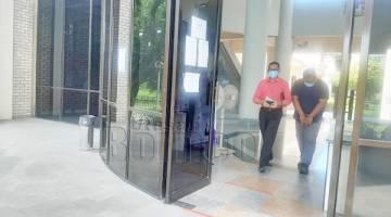 BERSALAH: Supardi (kanan) dibawa keluar dari kamar mahkamah.